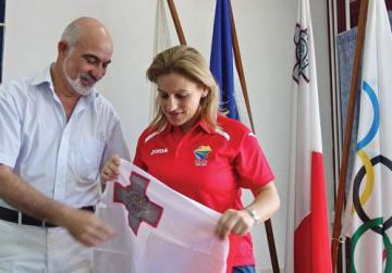 Eleonor Bezzina unfurling the Malta flag after it was passed on to her by MOC president Julian Pace Bonello.