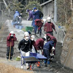 Volunteers carrying volcanic ash from an entrance of a residence in Miyakonojo, Miyazaki prefecture, yesterday.
