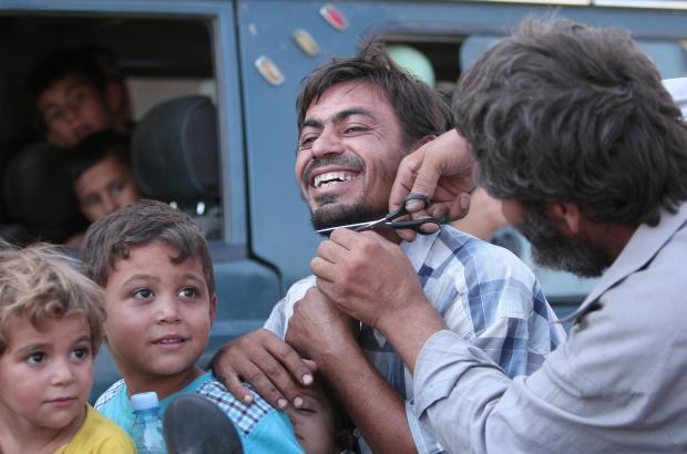 A man cuts the beard of a civilian who was evacuated.