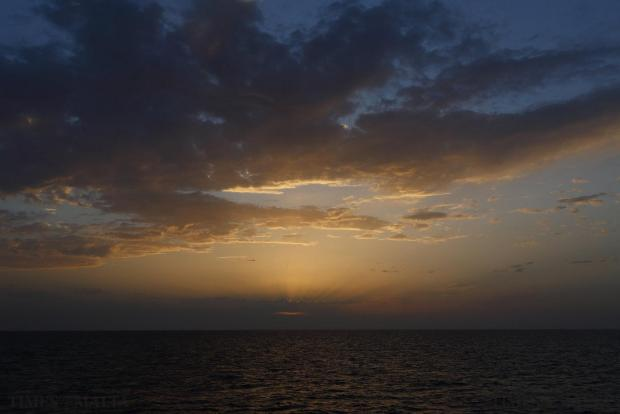 The sun sets over the area where a search for missing migrants was taking place after their boat capsized off the coast of Libya on August 5. A boat packed with up to 700 African migrants capsized in the Mediterranean Sea off the coast of Libya on Wednesday and many were feared dead, officials and aid agencies said. Photo: Darrin Zammit Lupi