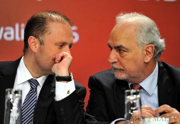 Prime Minister Joseph Muscat covers his mouth as he speaks to Deputy Prime Minister Louis Grech at the PL general conference on April 8. Photo: Chris Sant Fournier