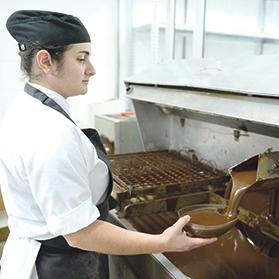 Cake decorator Marica Attard filling a mould with molten chocolate.
