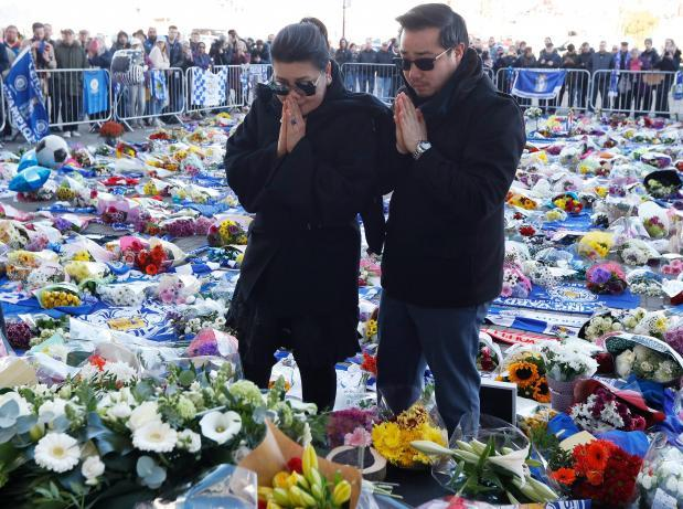 Khun Aiyawatt Srivaddhanaprabha, and Aimon Srivaddhanaprabha, son and wife of Leicester City's owner Thai businessman Vichai Srivaddhanaprabha, look at tributes at the King Power Stadium.