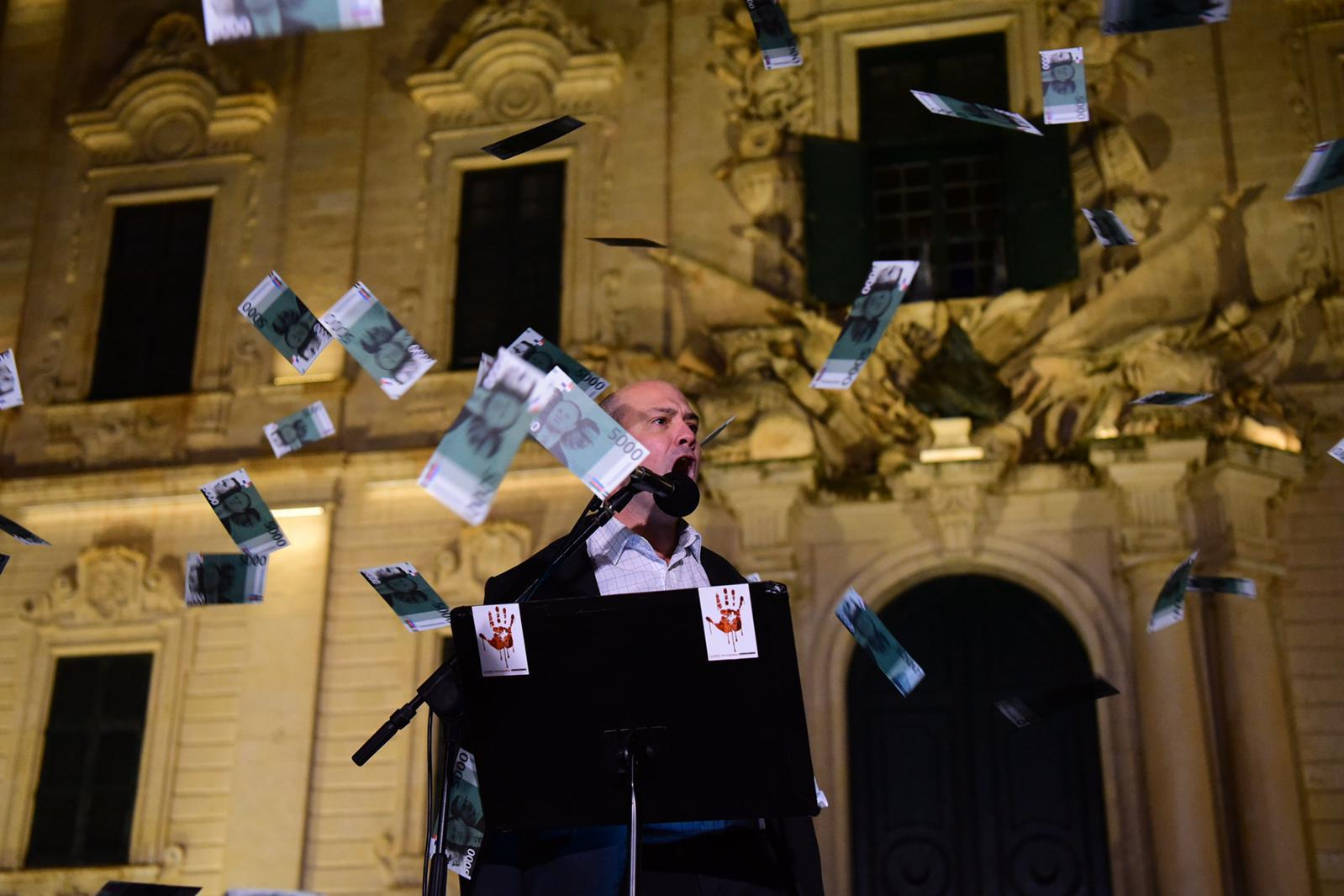 The crowd throws fake notes as speaker Norman Vella as he contrasts the hard work of the people with the government's actions. Photo: Mark Zammit Cordina