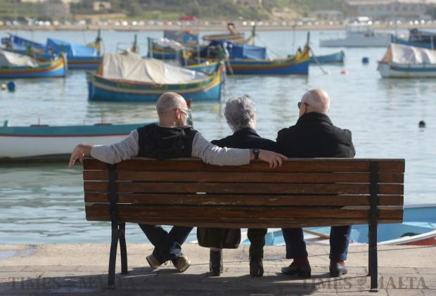 Three people enjoy the sun in Marsaxlokk on December 21. Photo: Matthew Mirabelli