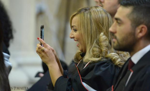 A graduate snaps a photo with her mobile at the Jesuit Church in Valletta on December 3. Photo: Matthew Mirabelli