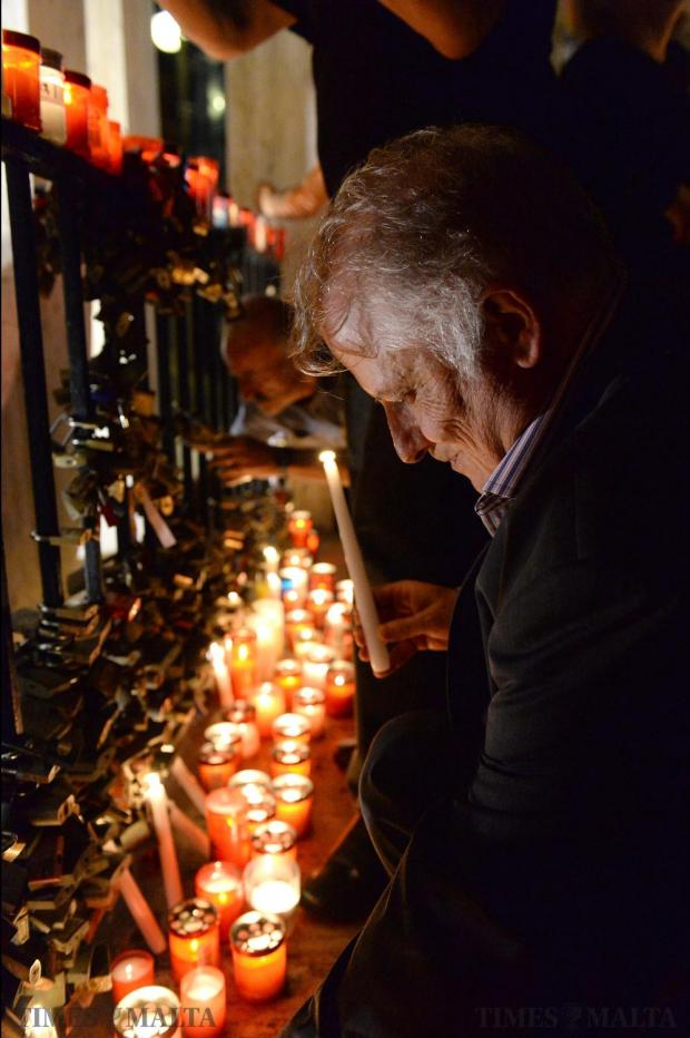 A man lights a candle during a candlelight vigil in Sliema on October 16, in tribute to late journalist Daphne Caruana Galizia who was killed by a car bomb close to her home in Bidnija, Malta. Photo: Matthew Mirabelli