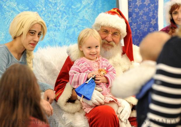Children pose for photographs with Santa Claus at The Point in Sliema on December 19. Photo: Chris Sant Fournier