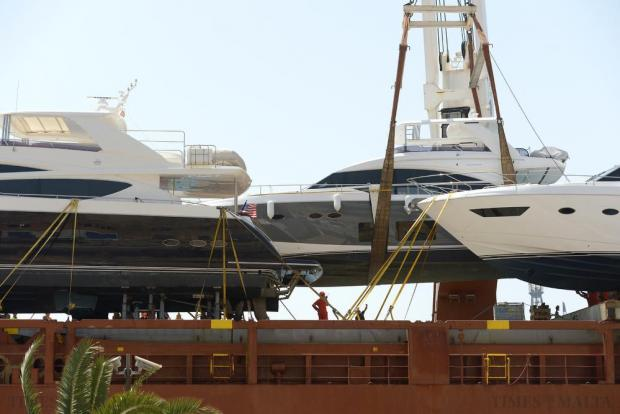 A luxury yacht is offloaded from a cargo vessel carrying several other large yachts at the Pinto Wharf in Valletta on June 14. Photo: Matthew Mirabelli