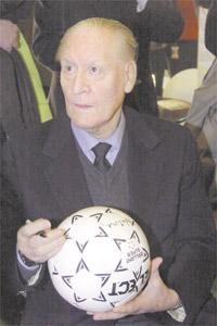 Nils Liedholm signs a football in this February 18, 2004 file photo.