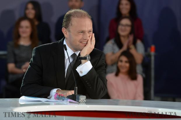 Joseph Muscat glances at a child after being given a flower during a television interview in San Gwann on May 5. Photo: Matthew Mirabelli