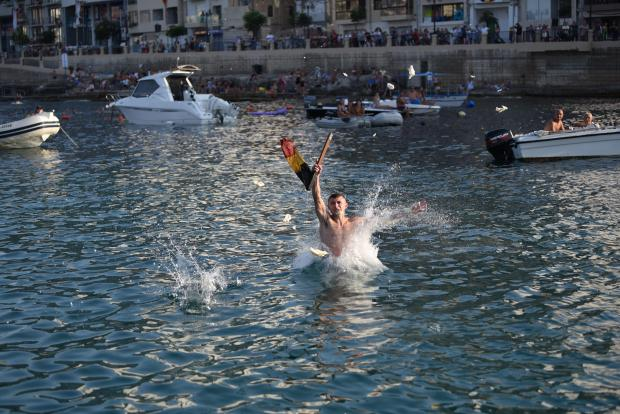 A competitor is caught entering the water moments after he grabbed first place during the annual Greasy pole competition held in St Julians on Aug 29. Photo: Mark Zammit Cordina
