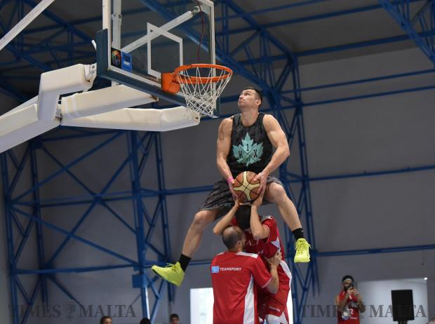 A basketball player jumps over another basketball player standing on a chair during a halftime at the Basketball Pavilion in Ta'Qali on November 25. Photo: Mark Zammit Cordina