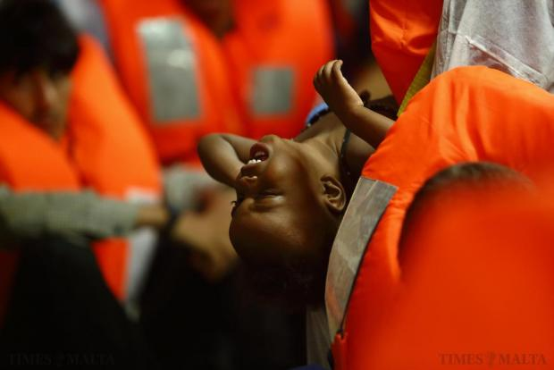 A migrant baby on the Migrant Offshore Aid Station (MOAS) ship MV Phoenix waits to be transferred to the Norwegian ship Siem Pilot off the coast of Libya on August 6. An estimated 600 migrants on an overloaded wooden boat were rescued 10.5 miles (16 kilometres) off the coast of Libya by the international non-governmental organisations Medecins san Frontiere (MSF) and MOAS without loss of life on Thursday afternoon, according to MSF and MOAS, a day after more than 200 migrants are feared to have drowned in the latest Mediterranean boat tragedy after rescuers saved over 370 people from a capsized boat thought to be carrying 600. Photo: Darrin Zammit Lupi