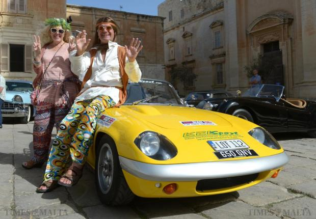 Two participants form the Mdina Grand Prix pose in front of a car at the Concourse d'Elegance outside the Cathedral in Mdina on October 9. Photo: Matthew Mirabelli