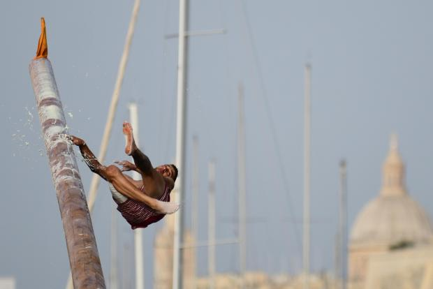 A young man loses his balance during the Gostra contest held as part of the St Joseph feast in Msida on July 23. Participants run across a pole covered in grease, lard and cactus extract in an attempt to collect flags. Photo : Jonathan Borg