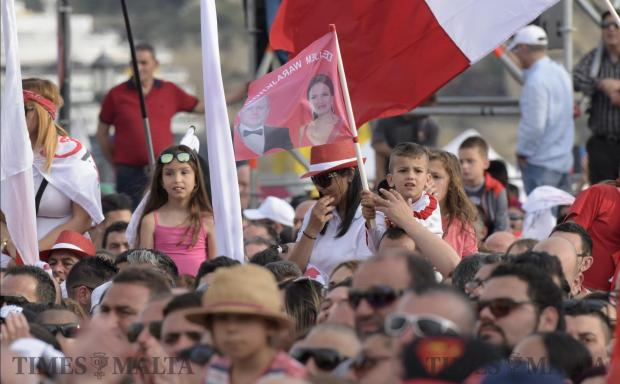 A child holds a flag with the faces of Prime Minister Joseph Muscat and his wife Michelle during the 1st May mass meeting in Valletta. Photo: Mark Zammit Cordina
