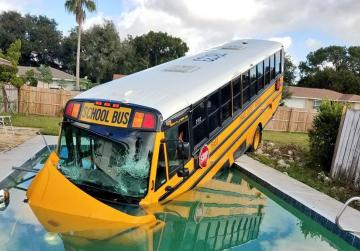 School bus ends up in swimming pool