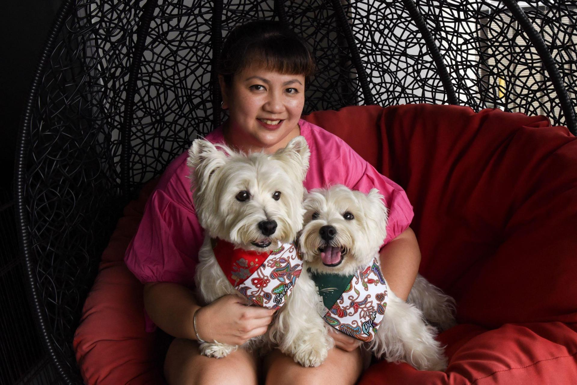 Dog owner Carrie Er with her pet white terriers Sasha and Piper (right) at her home in Singapore.