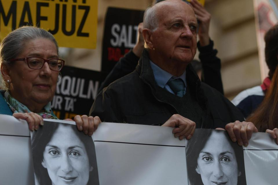 Daphne Caruana Galizia's parents hold photographs of their daughter at a recent anti-corruption protest. Photo Jonathan Borg