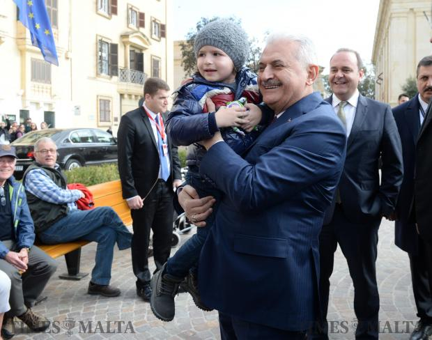 Turkish Prime Minister Binali Yildirim carries three-year-old Omer Tarik Balkan during his visit to Malta on February 17 as Economy Minister Chris Cardona (right) looks on. Photo: Matthew Mirabelli