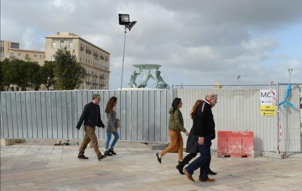 Pedestrians walk past construction hoarding towards Valletta on December 31, as the final touches are made in preparation Valletta for 2018. Photo: Matthew Mirabelli