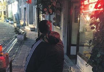 Turkish smuggler Dursun sitting in front of a shop in the Basmane district in the Aegean port city of Izmir.