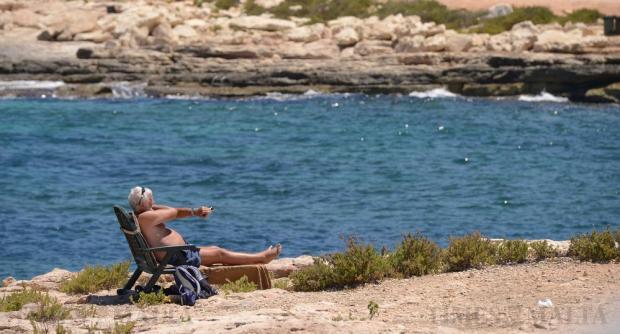 A man on a deck chair enjoys the sun in Baħar iċ-Ċagħaq on July 19. Photo: Matthew Mirabelli
