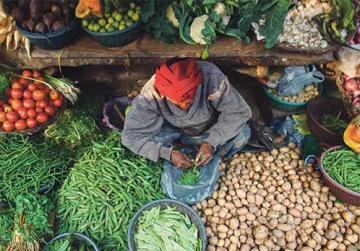 A man surrounded by vegetables and greens at his place at an Indian Bazaar.