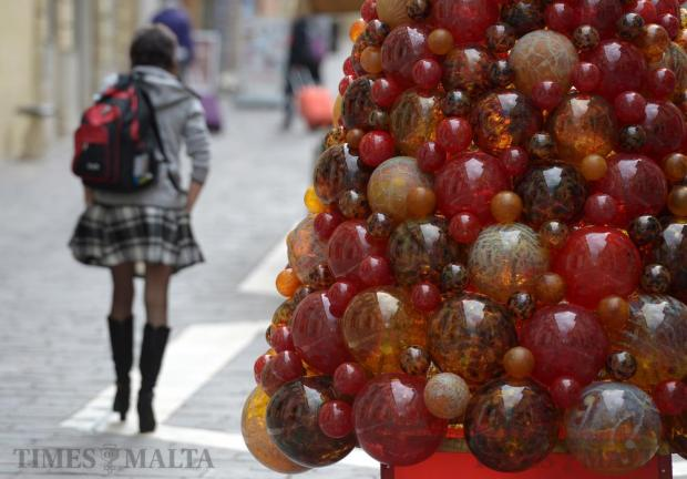 A woman makes her way past a Christmas tree made from glass balls in Valletta on November 29. Photo: Matthew Mirabelli