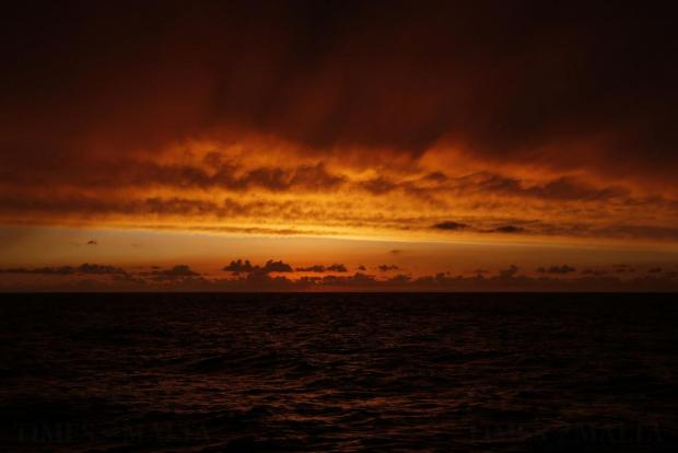 Sunset is seen from the Migrant Offshore Aid Station (MOAS) ship Topaz Responder as the ship stands-by for migrants in distress in international waters off the coast of Libya on June 21. Photo: Darrin Zammit Lupi