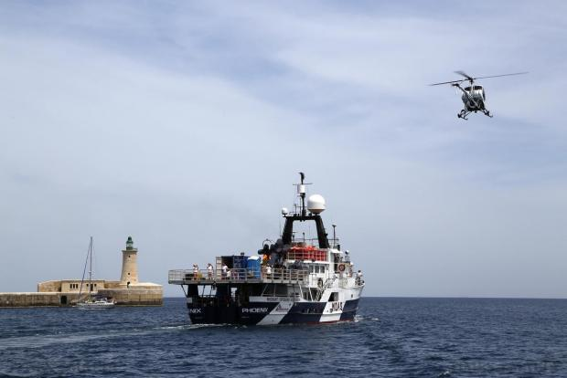 A helicopter flies overhead as the Migrant Offshore Aid Station (MOAS) ship MV Phoenix sails out of Valletta's Grand Harbour on May 2. The 40-metre ship MV Phoenix, manned by personnel from international non-governmental organisations Medecins san Frontiere (MSF) and MOAS, left Malta for a six-month mission to search for and rescue migrants in the Mediterranean. The Phoenix is the first privately funded vessel to operate in the Mediterranean. Photo: Darrin Zammit Lupi