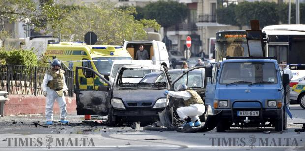 Forensic experts access the remains of a car after a car bomb went off in Msida on February 20. Photo: Mark Zammit Cordina