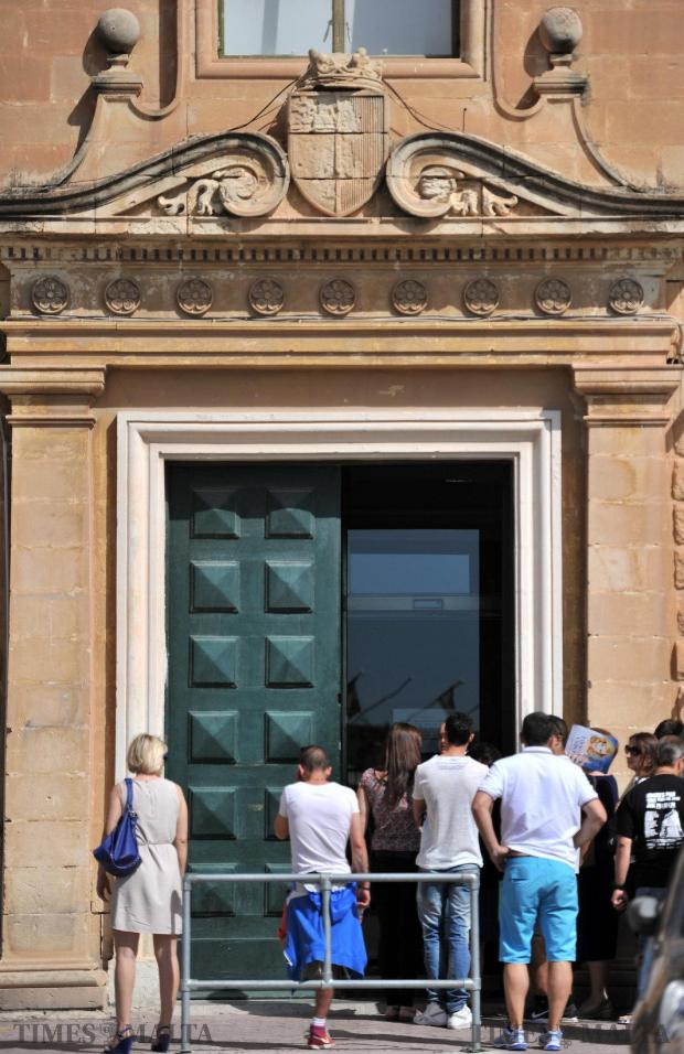 People wait to renew their identity card outside Evans Building in Valletta on May 14. Photo: Jason Borg
