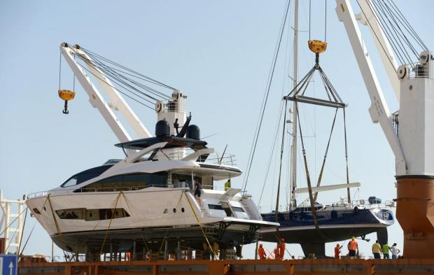 Luxury yachts are offloaded from a ship in the Grand Harbour, Valletta on September 30. Photo: Matthew Mirabelli