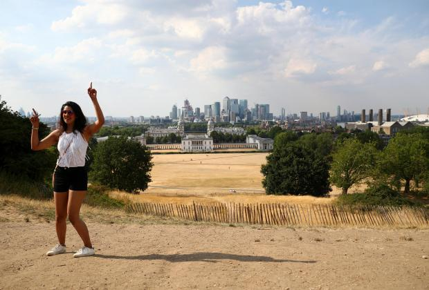 A woman poses for a picture with a backdrop of Canary Wharf and the City of London from Greenwich Park, London.
