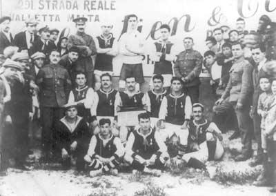 MFA XI played against the United Service League XI (1-1) on April 27, 1918. Standing: Salvu Troisi, Edwards, Karmenu Tabone. Sitting: Ruggieru Friggieri, Salvu Tabone, Sghendo, Zammit, Karmenu Cristiano. Squatting: Galea Sluta, C. Inglott, Emmanuel Busuttil.