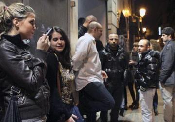Personas fumando afuera de un club nocturno en Madrid a primeras horas de ayer, después de que España introdujera una ley contra el tabaquismo que probablemente convierta al país de una tierra amigable con los cigarrillos con abundantes bares y restaurantes llenos de humo, a una de las zonas más estrictamente libres de humo de Europa.  Foto: Andres Kudacki / AP