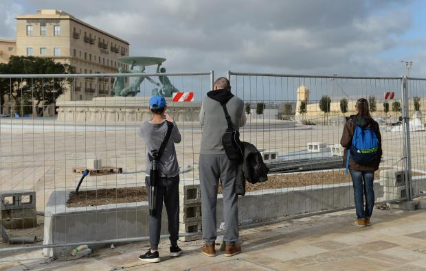 People take photos of the newly restored Triton Fountain at the entrance to Valletta on December 31. Photo: Matthew Mirabelli