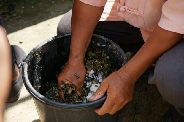 Uncle Plien mixes fish feed with locally harvested ingredients. Philip A. Loring
