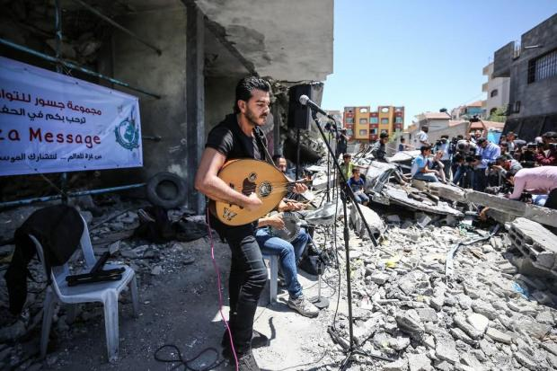 Palestinian singers perform traditional folk songs above the rubble of a residential building destroyed by Israeli warplanes during an impromptu concert in the blockaded Gaza Strip.