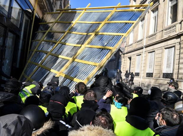 Yellow Vest protesters remove a window protection fence from a shop on the Champs-Elysee.