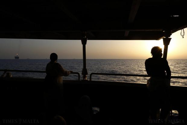 Rescued migrants on the deck of the Migrant Offshore Aid Station (MOAS) ship MV Phoenix look out at the Bouri Oil Field between Libya and the Italian island of Lampedusa, at sunset on August 3. 118 migrants were rescued by the Phoenix from a rubber dinghy some 32 kilometres off the coast of Libya on Monday morning. The Phoenix, manned by personnel from international non-governmental organisations Medecins san Frontiere (MSF) and MOAS, is the first privately funded vessel to operate in the Mediterranean. Photo: Darrin Zammit Lupi