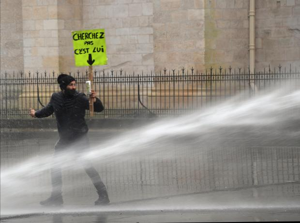 A protester is sprayed with a water cannon. Photo: AFP