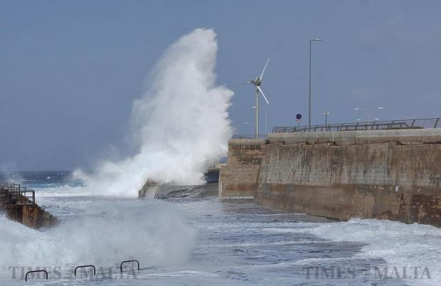 A wave rises high above a wind turbine at Cirkewwa on April 8. Photo: Chris Sant Fournier