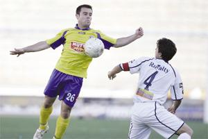 Marsaxlokk`s Cleaven Frendo leaps to chest the ball as Sliema`s Brian Said looks on.