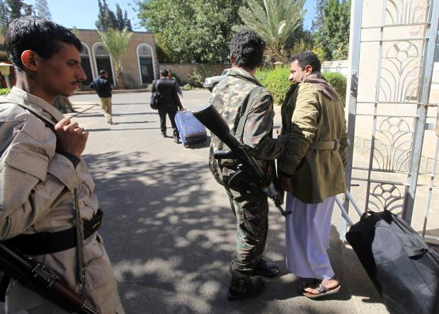 A relative of a Houthi delegation member participating in the negotiations in Sweden carries a bag at Sanaa airport.