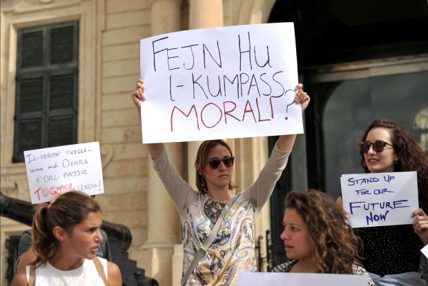 A woman holds up a placard at a protest by artists over the killing of Journalist Daphne Caruana Galizia outside Castille on October 21. Photo: Chris Sant Fournier