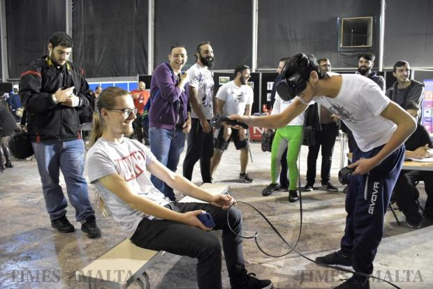 A man sitting on a bench moves backwards so as not to get hit by a person playing a virtual reality game at the Malta Comic Convention in Ta' Qali on December 3. Photo: Mark Zammit Cordina