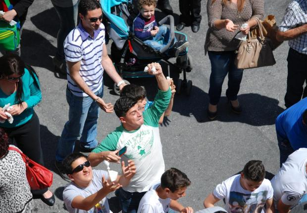 A teenage boy is caught on camera just moments after he caught a bag paper filled with ravjoli at the Ravjoli feast held in Mqabba on April 26. Photo: Mark Zammit Cordina